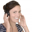 Young happy girl listens to music with headphones — Stock Photo