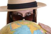 Jeune femme avec le globe et lunettes de soleil — Photo