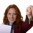 Woman with keys smiling — Stock Photo