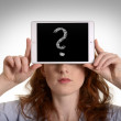 Pretty red-haired woman holding mini tablet pc with question mar — Stock Photo