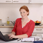 Pretty red-haired woman working in her home office — Stok fotoğraf