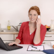 Foto Stock: Pretty red haired Womcalling in Home Office