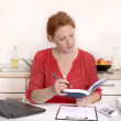 图库照片: Pretty red haired Womworking in Home Office