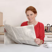 Pretty red haired woman reading newspaper — Stock Photo