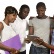 Four african friends looking at tablet PC — Stock Photo