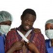 Stock Photo: Doctors threaten patient with knifes