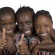 Three african kids holding thumbs up — ストック写真