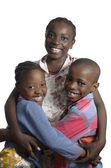 Three african kids holding on another smiling — Stock Photo