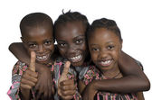 Three african kids holding thumbs up — Stock Photo