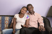 Young african couple on sofa — Stock Photo