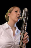 Pretty young woman playing bass clarinet — Stock Photo