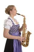 Woman in dirndl dress playing saxophone — Stock Photo