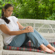 Stock Photo: Young WomRelaxing On Porch 5