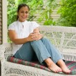 Stock Photo: Young WomRelaxing On Porch 6