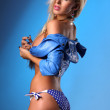 Stock Photo: Sexy busty blonde young womposing in blue leather jacket