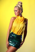 Sexy young woman posing in a green skirt and a yellow shirt — Stock Photo