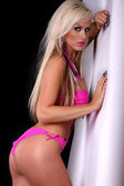 Sexy blonde young woman posing in a pink bikini — Stock Photo