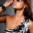 Portrait of a young woman in a black-white dress with sunglasses — Stock Photo