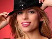 Portrait of a beautiful young woman wearing a red bra and a black hat — Stock Photo