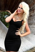 Sexy busty blonde young woman posing outdoor in black outfit — Stock Photo