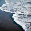 Foamy wave on black sand beach. — Stock Photo #31073931