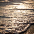 Stockfoto: Foaming waves on beach at sunset.