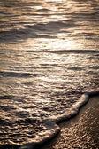 Onde spumeggianti sulla spiaggia al tramonto. — Foto Stock
