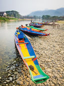 Colorful wooden longboats in Vang Vieng, Laos. — Stockfoto