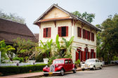 A traditional wooden building and classic cars in Luang Prabang. — Stock Photo