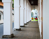 Red tuk tuk and white columns inside Galle Fort. — Stock Photo