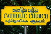 Trilingual sign for Catholic Church. — Stok fotoğraf