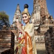 Stock Photo: Womperforming typical thai dance with thai style temple background