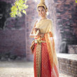Woman wearing typical thai dress with thai style temple background — Stock Photo