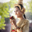 Woman wearing typical thai dress with thai style temple background — Stock fotografie