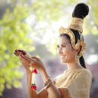 Woman wearing typical thai dress with thai style temple background — Stock Photo #27641831