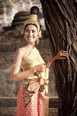 Femme vêtue d'une robe thaïe typique avec fond de temple de style thaïlandais — Photo