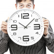 Time concept,Businessman holding big clock and give the expression on his face — Stock Photo