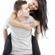 Portrait of a happy young man giving a piggyback ride to her girlfriend against white background — Stock Photo