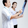 Male and female doctor looking at patient xray film. — Stock Photo #28021323