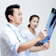 Male and female doctor looking at patient xray film. — Stock Photo #28021327