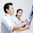 Male and female doctor looking at patient xray film. — Stock Photo #28021341