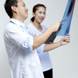 Male and female doctor looking at patient xray film. — Stock Photo #28021431