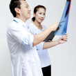 Male and female doctor looking at patient xray film. — Stock Photo