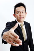 Happy businessman with an open hand ready to seal a deal. Isolated on white background. — Stock Photo