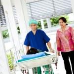 将她的表妹患者对医院的推车移动到手术室的医务工作者 — 图库照片 #28081549
