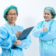 Smiling female medical doctor and nurse with stethoscope and clipboard — Stock Photo