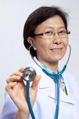 улыбаясь пожилая женщина врач со стетоскопом. — Стоковое фото