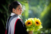 Young graduation woman with yellow flowers — Stock Photo