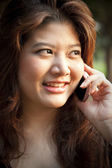 Portrait of a cheerful young woman using the cellphone — Stock Photo