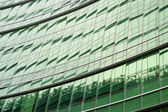 Modern green glass skyscraper perspective view — Stock Photo